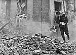 An Air Raid Warden runs across a large pile of rubble during Civil Defence training in Fulham during 1942. D7873.jpg