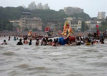 A Ganesha statue on the water, surrounded by people