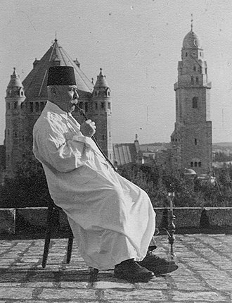 Armenian Quarter - An Armenian priest in Jerusalem c. 1900 pictured smoking a hookah with the Dormition Abbey in the background
