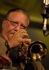 A man with glasses is playing a trumpet in front of the camera.