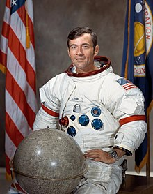 Official photograph of Young in an Apollo spacesuit with a globe of the Moon