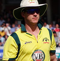 A man in yellow-jersey wearing glasses and a white hat.