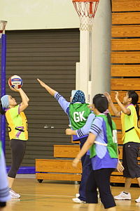 Adult women from Brunei playing netball. One team is wearing green and the other team is wearing yellow. The game is being played indoors on wooden floors. The players are all wearing pants. Some have coverings over their heads. The yellow team is in act of shooting and the green team is trying to block the shot.