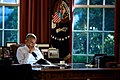 Barack Obama engrossed in reading at the Resolute Desk while illuminated by some interesting, autumnal, western sunlight falling through the garden windows (31901910102).jpg