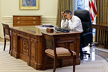 Barack Obama on the phone while sitting at the Resolute desk in 2009. The wooden box holding the button is visible next to the phone.
