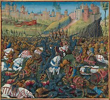 A dozen armed horsemen fight against each other on a field covered by bodies at a large castle on a hill