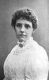 Black-and-white portrait of a white woman in a high-necked white dress