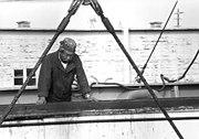 The bosun aboard a modern merchant ship stands cargo watch as freight is lowered into an open hatch.