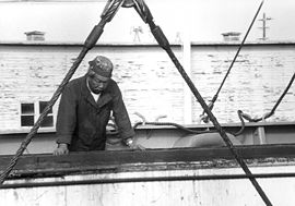 The boatswain aboard a modern merchant ship stands cargo watch as freight is lowered into an open hatch.