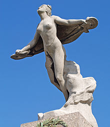 A photograph from ground level looking up towards a memorial statue of a flying woman on top of a pillar. She is nude, her arms are outstretched with a drape or wing behind her, and her face is lifted towards the sky.