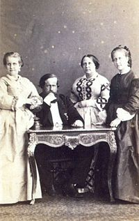 A photograph showing a bearded man seated at a table with an older woman with dark hair standing immediately to his left, and two younger women in long, mid-Victorian dresses standing one at the left side of the table and one at the right side of the table