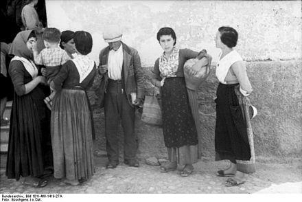 1943: gruppo di uomini e donne fotografati in un paese del sud Italia