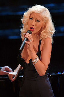 A blonde woman holding a microphone wearing a black dress.
