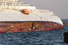 Ship lying on the side, hull gash with boulder is seen below exposed waterline of ship