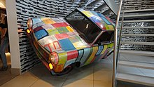 A car with bright coloured squares painted on the exterior is tilted slightly to its left side at the bottom of a spiral staircase.