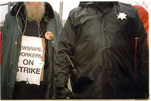 Conference of Newspaper Unions member on strike November 3, 1994 stands next to a San Francisco police officer.jpg