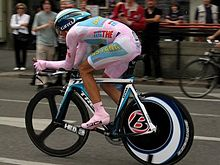 A man in pink clothes and pink shoes, sitting ducked down on a bicycle. In the background people are watching.