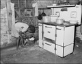 Daughter of Lawson Mayo, disabled miner, in the kitchen of the four room house in which two adult and ten children... - NARA - 540969.tif