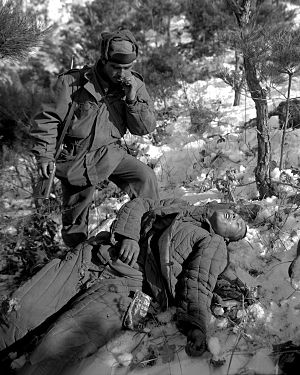 Operation Courageous - A US soldier examines a dead Chinese soldier killed during the offensive drive of the 5th RCT near the Han River area, Korea.