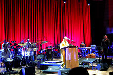 An ensemble are performing on-stage, three musicians are seated at extreme left behind musical instruments. Lisa Gerrard is behind a lectern near mid-stage with a microphone. At the right is Brendan Perry holding a microphone with his left hand. His right hand is alongside his thigh and holding an instrument. The background includes a long stage curtain with another musician seated at rear right, who is obscured behind a keyboard.