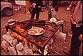 Deer Hunters Prepare Their Evening Meal at the Permanent Camp They Have Constructed near Wild Deer Feeding Places. 11-1972 (3703565007).jpg
