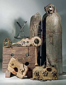 Colour photograph of many traditional instruments of torture, including a variety of stocks and an Iron Maiden.