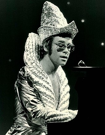 Elton John often wore elaborate stage costumes as part of the glam rock era in the UK music scene. Elton john cher show 1975.JPG