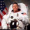 man in space suit holding helmet, American flag in background