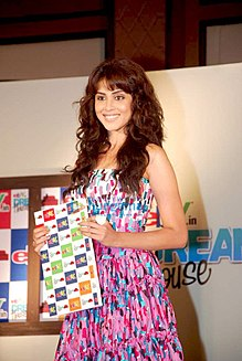 A smiling girl, her hair in a loose bun and long brownish bangs, poses on stage in a coloured outfit, holding a book