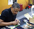 Giancarlo Esposito signing photos with his autograph.jpg