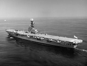 Side view of an aircraft carrier in motion. A helicopter sits on the carrier's deck, and several dark-uniformed people can also be seen.