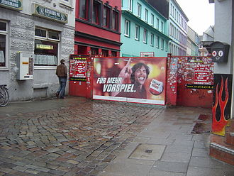 """Herbertstraße - Entrance to Herbertstraße; red sign to the right of the gate reads """"No entrance for juveniles under 18 years of age and women"""". The large cigarette ad reads literally, """"...For more foreplay."""""""