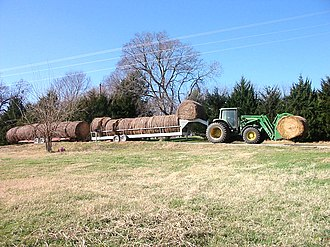 Grayson County, Texas - A rancher transports round bales of hay down a rural road in Grayson County, Texas. The economy of the county relies in part upon agriculture and ranchers.
