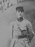 A portrait of a young man dressed in a legionnaire's cap and uniform coat, standing at ease.