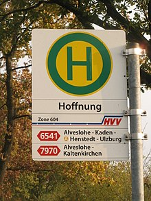 A street sign with the letter H in a circle