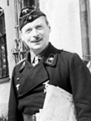 A smiling man in a black uniform holding s sheaf of documents