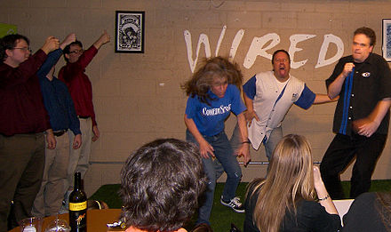 ComedySportz Austin performing a shortform game based on direction from the audience with the help of Red Dirt Improv; in this case spoofing a hard rock band performing a song made up on the stage Improv austin 2009.jpg