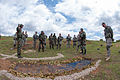 Indian and U.S. Army officers evaluate a recently concluded simulated combat patrol at a scale model of the patrol area at Fort Bragg, N.C..jpg