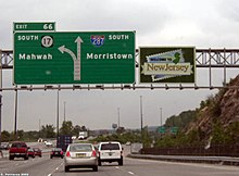 A multilane freeway approaching an interchange with a sign display over the road. The left sign reads exit 66 south Route 17 Mahwah left two lanes exit Interstate 287 south Morristown right two lanes straight and the right sign says Welcome to New Jersey