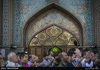 Iranian architecture - Congregational prayer before the arched entrance to Imamzadeh Saleh Shrine interior, Tehran, 2017.