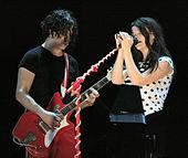 Sur la gauche, un homme en pantalon rouge et un T-shirt noir avec des cheveux noirs jusqu'au menton tenant une guitare rouge.  À droite, une femme vêtue d'une chemise blanche à pois noirs se tient derrière un pied de micro rouge.