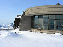 Surrounding a curved building with glass windows is a landscape of snow.