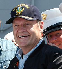 A man wearing a cap smiles broadly.