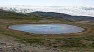 Kettle (round glacial eye-shaped lake), highlands of Isunngua, Greenland.