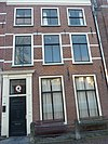 foto van Pand met bakstenen gevel met rechte kroonlijst, deuromlijsting Lod. XV op metselwerk van verdieping resten van geverfde banden. Hardstenen stoep met palen