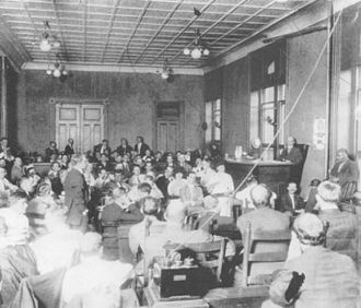 Parade (musical) - The first day of the trial. Spectators were racially segregated. The stenographer can be seen next to Newt Lee, who is being questioned by prosecutor Hugh Dorsey.