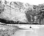 Lituya Glacier, terminus of tidewater glacier in the background and a man in a boat in the foreground for scale, undated (GLACIERS 5616).jpg