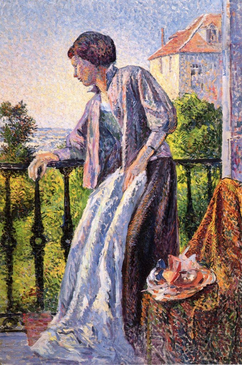 Femme en robe longue regardant dehors, appuyée sur le garde-corps en fer forgé.