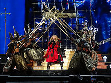 Madonna in a red kimono-like dress in the middle of the stage, flanked by dancers in Samurai costumes holding up giant crosses above her.