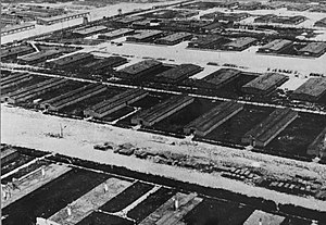 Majdanek concentration camp - Aerial reconnaissance photograph of the Majdanek concentration camp (June 24, 1944) from the collections of the Majdanek Museum; lower half: the barracks under deconstruction with visible chimney stacks still standing and planks of wood piled up along the supply road; in the upper half, functioning barracks